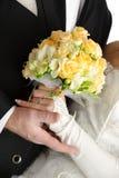Hochzeitsblumenstrauß in den Händen der Braut und des Bräutigams, auf wh Stockfotografie