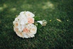 Hochzeitsblumenstrauß, der auf das Gras legt lizenzfreies stockfoto
