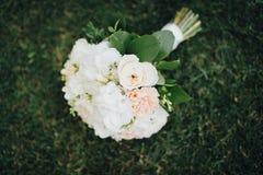 Hochzeitsblumenstrauß, der auf das Gras legt stockfoto
