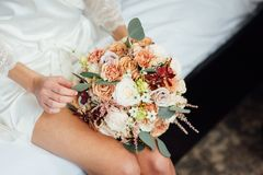 Hochzeitsblumenstrauß in Korb Eine Frau in einem weißen Heiratskleid, das einen Blumenstrauß von Blumen in ihren Händen hält stockfotografie