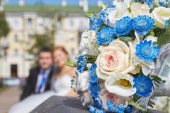 Hochzeitsblumenstrauß liegt auf dem Hintergrund der Jungvermählten Stockfotografie