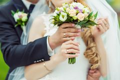 Hochzeitsblumenstrauß mit empfindlichen rosa, beige, weißen Blumen mit grünen Blättern in den Händen der Bräute im Kleid und Kost lizenzfreie stockfotografie