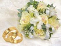 Hochzeitsblumenstrauß mit Goldhochzeitsringen auf weißem b Lizenzfreie Stockfotos