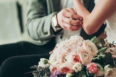 Hochzeitsblumenstrauß mit unscharfer Braut und Bräutigam im Hintergrund stockfotografie