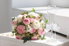 Hochzeitsblumenstrauß und Champagnerglas stockbild