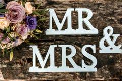 Hochzeitsblumenstrauß und -ringe auf Holzoberfläche Stockfotografie