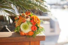 Hochzeitsblumenstrauß von den weißen, orange Blumen, Rosen liegt unter einem p Stockfotografie