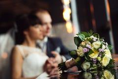 Hochzeitsblumenstrauß von gelben Rosen und von purpurroten Blumen mit der Braut und Bräutigam verwischt im Restauranthintergrund Stockfotos
