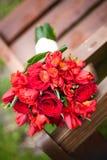 Hochzeitsblumenstrauß von gemischten roten Rosen auf einer Bank Stockbild