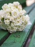 Hochzeitsblumenstrauß von Rosen mit Ringen auf Holzbank Stockfotos