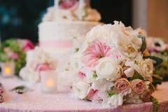 Hochzeitsblumenstrauß von Rosen vor Hochzeitstorte. Stockbild