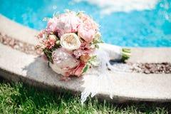 Hochzeitsblumenstrauß von Weiß und von rosafarbenen Blumen auf dem Boden Lizenzfreies Stockbild