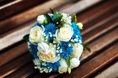 Hochzeitsblumenstrauß von weißen Rosen und von blauen Chrysanthemen auf einer braunen Holzbank, ein Blumenstrauß der Braut Lizenzfreie Stockfotos