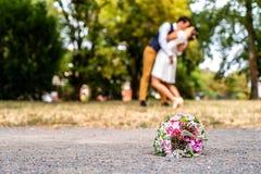 Hochzeitsblumenstrauß vor Jungvermählten verbinden den Hintergrund und küssen flache Tiefe bokeh lizenzfreie stockfotos