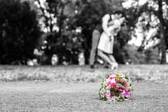 Hochzeitsblumenstrauß vor Jungvermählten verbinden den Hintergrund und küssen flache Tiefe bokeh lizenzfreie stockfotografie