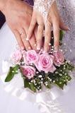 Hochzeitsblumenstraußtenderrosen, -hände und -ringe Lizenzfreie Stockfotos