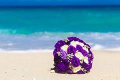 Hochzeitsblumenstrauß, der auf dem Sand auf einem tropischen Strand liegt Blaues Meer Stockfotos