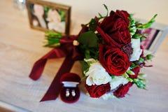 Hochzeitsblumenstrauß der roten und weißen Rose und des Bandes mit Hochzeit ri Lizenzfreies Stockbild