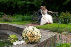 Hochzeitsblumenstrauß mit Braut und Bräutigam im Hintergrund Stockfotos