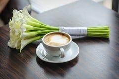Hochzeitsblumenstrauß von Callalilien auf einer Tabelle mit einem Tasse Kaffee Lizenzfreie Stockfotos