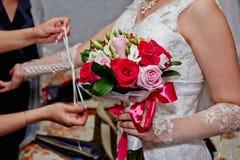 Hochzeitsblumenstrauß von den roten Rosen in einer Hand an der Braut Stockbilder