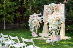 Hochzeitsbogen draußen verziert mit Stoff und Blumen Schöne Hochzeitseinrichtung Hochzeitszeremonie auf grünem Rasen in Stockbild