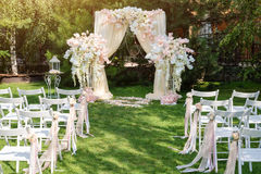 Hochzeitsbogen draußen verziert mit Stoff und Blumen Schöne Hochzeitseinrichtung Hochzeitszeremonie auf grünem Rasen in Stockbilder
