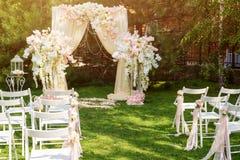 Hochzeitsbogen draußen verziert mit Stoff und Blumen Schöne Hochzeitseinrichtung Hochzeitszeremonie auf grünem Rasen in Stockfotos
