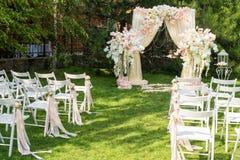 Hochzeitsbogen draußen verziert mit Stoff und Blumen Schöne Hochzeitseinrichtung Hochzeitszeremonie auf grünem Rasen in Stockfotografie