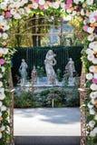 Hochzeitsbogen mit Blumen draußen Schöne Hochzeitseinrichtung Hochzeitszeremonie im Garten mit Skulpturen und Lizenzfreies Stockfoto