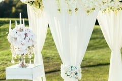 Hochzeitsbogen mit Blumen und Ñ- andle Dekoration am sonnigen Tag im Zeremonieplatz lizenzfreie stockbilder