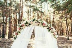 Hochzeitsbogen mit den Blumen aufgestellt im Wald auf Hochzeitszeremonie lizenzfreie stockfotografie