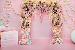 Hochzeitsbogen zuhause Festliche Dekorationen mit Blumen und bunten Ballonen auf rosa Hintergrund Stockfotografie