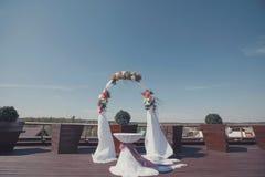 Hochzeitsbogenlaube mit weißem Stoff und Blumen Zeremonietabelle Stockbild
