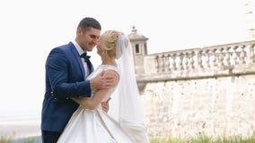 Hochzeitsbraut und -bräutigam, die vor dem alten Schloss küssen stock video footage
