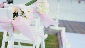 Hochzeitsdekor auf den Stühlen, den Bändern und der Blume auf weißen Stühlen, Rosen und wilden Blumen in den kleinen Vasen in der stock footage
