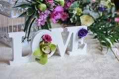 Hochzeitsdekor, -Liebesbriefe und -blumen auf Tabelle Frische Blumen und LIEBES-Dekoration auf festlicher Tabelle Luxuriöse Hochz Stockfotos