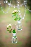 Hochzeitsdekor mit Eheringen und Rosen in den Birnen Lizenzfreies Stockbild