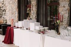 Hochzeitsdekoration der Tabelle mit roten Kerzen, Kerzenständer, weiße Platten Lizenzfreies Stockbild