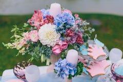 Hochzeitsdekoration im Stil des boho, Blumengesteck, verzierte Tabelle im Garten Hände der Braut und des Bräutigams Stockfotos