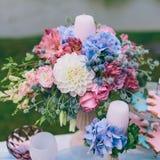 Hochzeitsdekoration im Stil des boho, Blumengesteck, verzierte Tabelle im Garten Hände der Braut und des Bräutigams Lizenzfreie Stockfotos
