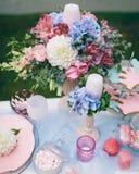 Hochzeitsdekoration im Stil des boho, Blumengesteck, verzierte Tabelle im Garten Hände der Braut und des Bräutigams Stockbild