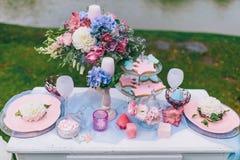 Hochzeitsdekoration im Stil des boho, Blumengesteck, verzierte Tabelle im Garten Hände der Braut und des Bräutigams Lizenzfreie Stockfotografie