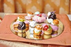 Hochzeitsdekoration mit farbigen kleinen Kuchen, Meringen und Muffins Elegante und luxuriöse Ereignisanordnung mit bunten Kuchen Stockbild