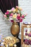 Hochzeitsdekoration mit mehrfarbigen Rosen im Vase, Pastell färbte kleine Kuchen, Meringen, Muffins und macarons lizenzfreies stockfoto