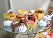 Hochzeitsdekoration mit Pastell färbte kleine Kuchen, Meringen, Muffins und macarons Lizenzfreie Stockfotografie