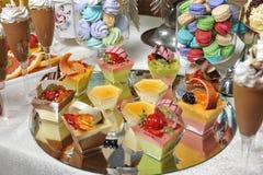 Hochzeitsdekoration mit Pastell färbte kleine Kuchen, Meringen, Muffins und macarons Stockfotos