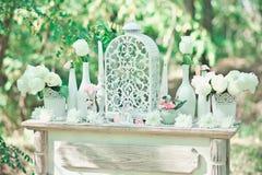 Hochzeitsdekorationen für die Zeremonie in den weißen Blumen auf grünem Hintergrund, Kerzen, Geschirr Lizenzfreies Stockbild