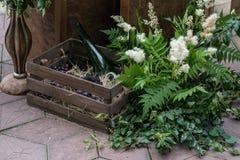 Hochzeitsdekorationen mit Blumen-, Holzkiste- und Weinflaschen Rustikale Art Stockfotos