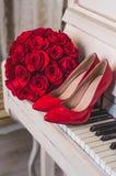 Hochzeitsdetails: Blumenstrauß von Blumen der roten Rosen und die Schuhe der Braut stehen auf klassischem weißem Klavier Stockbilder